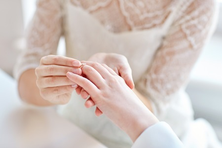 homosexual sex: people, homosexuality, same-sex marriage and love concept - close up of happy lesbian couple hands putting on wedding ring