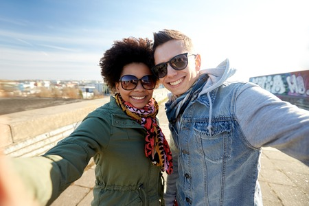 multiracial: tourism, travel, people, leisure and technology concept - happy teenage international couple taking selfie on city street
