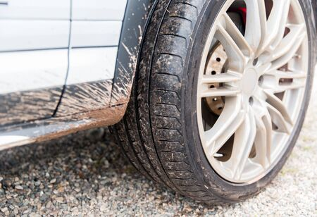 dirty car: transport, driving and motor vehicle concept - close up of dirty car wheel on ground