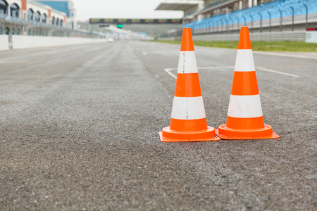 racing, motosports, extreme and motoring concept - traffic cones on speedway of stadium Stock Photo