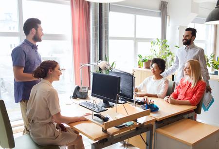 bedrijfsleven, opstarten en mensen concept - gelukkig creatieve team praten in het kantoor Stockfoto