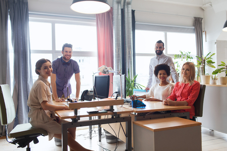 working space: business, startup and people concept - happy creative team in office