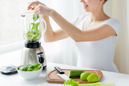 건강한 식생활, 요리, 채식 음식, 다이어트와 사람들 개념 - 가까이 집에서 해독 쉐이크 나 스무디를 만드는 믹서기와 녹색 야채와 함께 젊은 여자가 스톡 콘텐츠