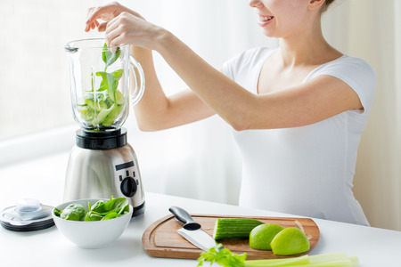 healthy eating, cooking, vegetarian food, dieting and people concept - close up of young woman with blender and green vegetables making detox shake or smoothie at home