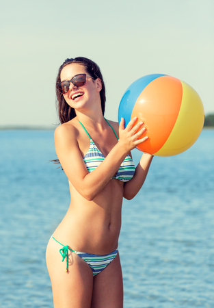 teenage girl: sea, summer vacation, holidays, sport and people concept - smiling teenage girl sunglasses with inflatable ball on beach