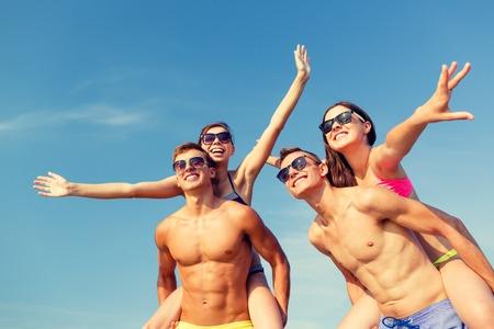 vacaciones en la playa: amistad, el mar, las vacaciones de verano, las vacaciones y la gente concepto - grupo de amigos sonrientes que usan trajes de baño y gafas de sol que se divierten en la playa