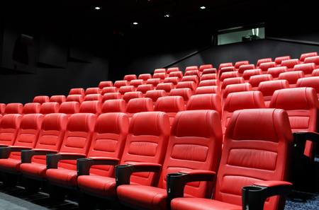hollywood movie: entertainment and leisure concept - movie theater or cinema empty auditorium with red seats Stock Photo