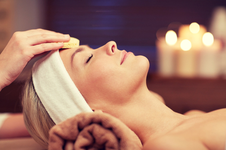 people, beauty, spa, cosmetology and relaxation concept - close up of beautiful young woman lying with closed eyes having face cleaning by sponge in spa Archivio Fotografico