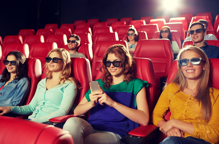 movies: cinema, technology, entertainment and people concept - happy woman with 3d glasses and smartphone reading message in movie theater