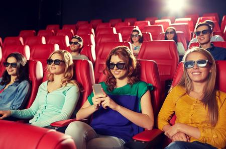 cine: el cine, la tecnolog�a, el entretenimiento y la gente concepto - mujer feliz con gafas 3d y lectura de mensajes de tel�fonos inteligentes en cine