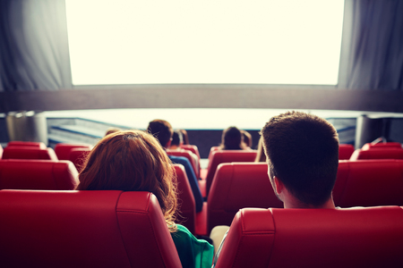 girlfriend: cinema, entertainment, leisure and people concept - couple watching movie in theater from back