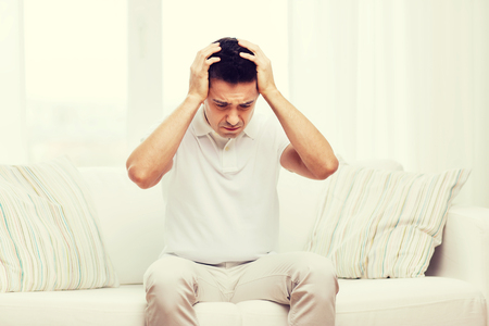 unhappy people: people, crisis, emotions and stress concept - unhappy man suffering from head ache at home Stock Photo