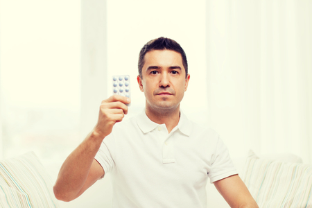 home health care: people, medication, medicine and health care concept - man showing pack of pills at home Stock Photo