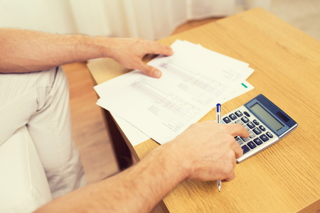 calculator: business, savings, finances and people concept - close up of man hands with papers and calculator at home