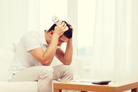 persona triste: Negocios, ahorros, crisis financiera, gente, concepto - hombre, dinero, calculadora, hogar Foto de archivo