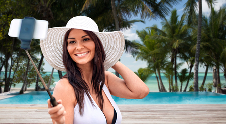 pool stick: lifestyle, leisure, summer, technology and people concept - smiling young woman in sun hat taking picture with smartphone on selfie stick over tropical beach with palms and swimming pool background