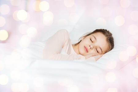 wellness sleepy: people, children, rest and comfort concept - girl sleeping in bed over lights Stock Photo