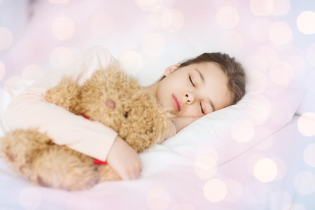 wellness sleepy: people, childhood, rest and comfort concept - girl sleeping with teddy bear toy in bed over lights