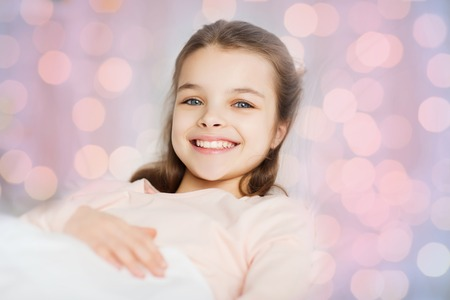 wellness sleepy: people, children, rest and comfort concept - happy smiling girl lying awake in bed over pink lights Stock Photo