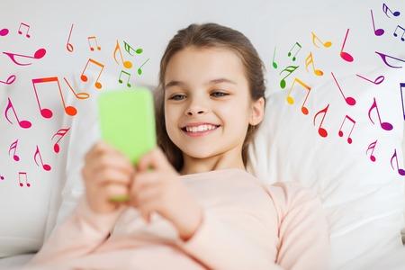 mignonne petite fille: les gens, les enfants, la musique et le concept de la technologie - heureuse jeune fille souriante éveillé smartphone dans le lit à la maison sur des notes de musique