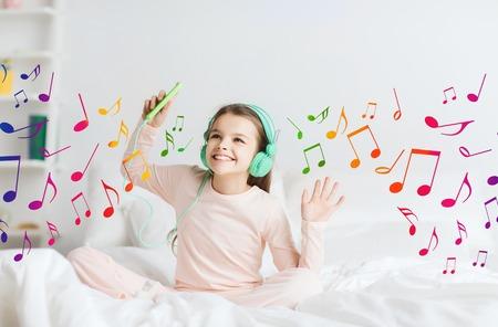 personas escuchando: la gente, los niños, fiesta de pijamas y concepto de la tecnología - niña sonriente feliz en los auriculares sentado en la cama con el teléfono inteligente y escuchar música en casa sobre las notas musicales