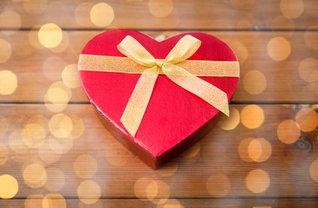 uprzejmości: love, date, romance, valentines day and holidays concept - close up of heart shaped gift box on wood