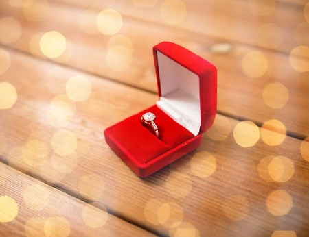 uprzejmości: proposal, engagement, valentines day and holidays concept - close up of red gift box with diamond engagement ring on wood