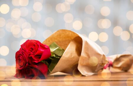 flirtation: love, date, flowers, valentines day and holidays concept - close up of red roses bunch wrapped into brown paper on wooden table