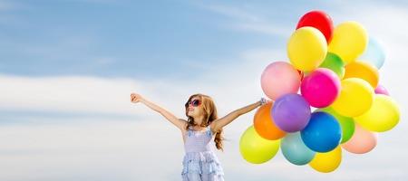 familias felices: vacaciones de verano, celebración, familia, niños y personas concepto - Niña feliz con los globos coloridos Foto de archivo