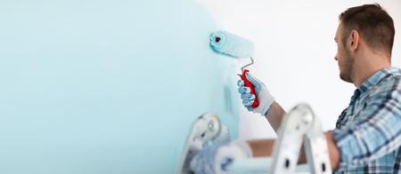 reparación, construcción y el hogar concepto - cerca del varón en los guantes de la celebración de rodillo de pintura Foto de archivo