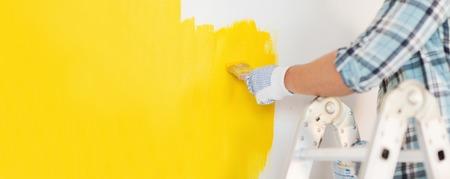 修理し改修コンセプトをホーム - 黄色のペンキで壁を塗る手袋で男性の手のクローズ アップ 写真素材