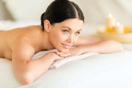 relaxation massage: health and beauty, resort and relaxation concept - woman in spa salon lying on the massage desk Stock Photo