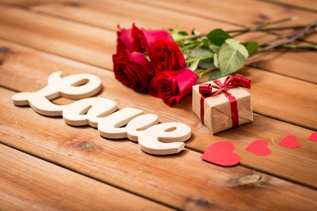 uprzejmości: love,  romance, valentines day and holidays concept - close up of gift box, red roses and hearts on wood Zdjęcie Seryjne