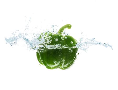 pimenton: verduras, los alimentos y la alimentación saludable concepto - cerca de pimienta verde fresca caída o inmersión en el agua con el chapoteo sobre fondo blanco Foto de archivo