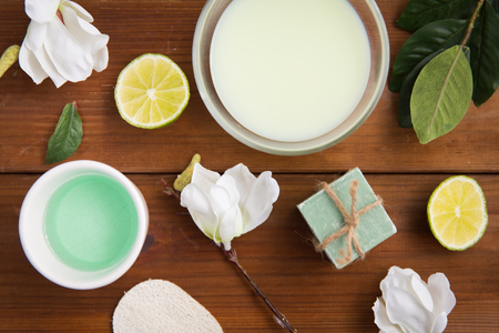 beauty, spa, body care and  natural cosmetics concept - close up of bowls with citrus body lotion, cream and soap on wooden table Stock Photo
