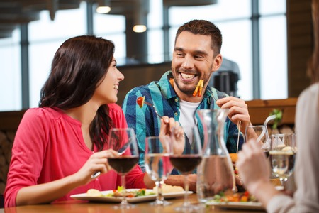 having lunch: leisure, people, eating and holidays concept - happy couple with friends having dinner at restaurant