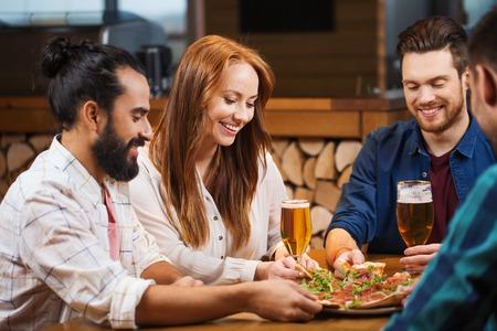 restaurante italiano: ocio, alimentación y bebidas, la gente y el concepto de vacaciones - sonriendo amigos comiendo pizza y bebiendo cerveza en el restaurante o la pizzería