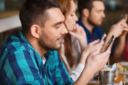 family and friends: leisure, technology, lifestyle and people concept - happy friends with smartphones dining at restaurant