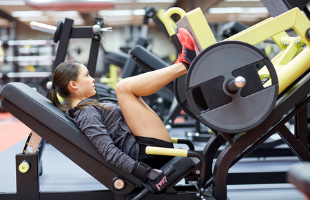 asian bodybuilder: fitness, sport, bodybuilding, exercising and people concept - young woman flexing muscles on leg press machine in gym