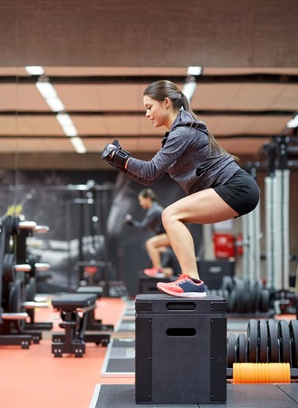 squats: fitness, sport, exercising and people concept - woman doing squats on pnatfom in gym Stock Photo