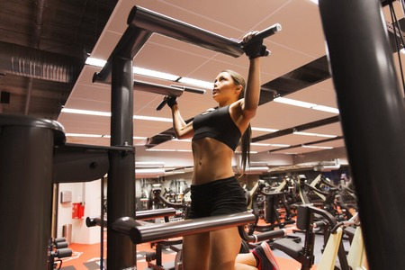 pullups: sport, fitness, lifestyle and people concept - woman exercising and doing pull-ups in gym Stock Photo