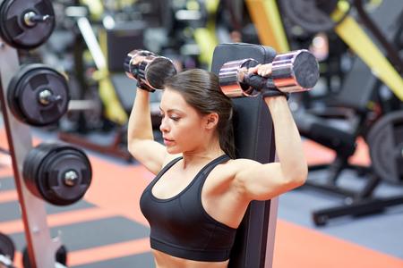 lo sport, il fitness, culturismo, sollevamento pesi e la gente concetto - giovane donna con manubri flette i muscoli in palestra dal retro Archivio Fotografico