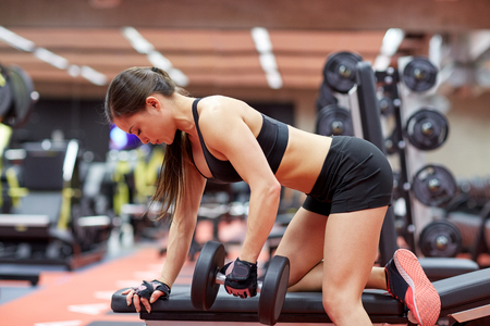 fitness gym: sport, fitness, bodybuilding, weightlifting and people concept - young woman with dumbbell flexing muscles in gym from back