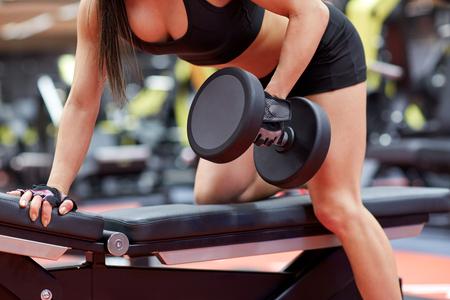 hilera: deporte, fitness, culturismo, levantamiento de pesas y el concepto de la gente - cerca de la mujer joven con mancuernas flexionando los músculos en el gimnasio de la parte posterior