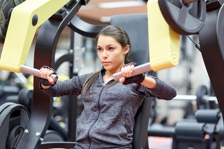 active lifestyle: fitness, sport, bodybuilding, exercising and people concept - young woman flexing muscles on seated chest press machine in gym Stock Photo