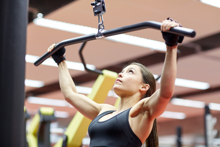 woman muscle: sport, fitness, bodybuilding, lifestyle and people concept - woman flexing arm muscles on cable machine in gym