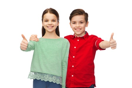 pre approval: childhood, fashion, gesture and people concept - happy smiling boy and girl hugging and showing thumbs up