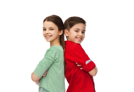 childhood, fashion and people concept - happy smiling boy and girl standing back to back