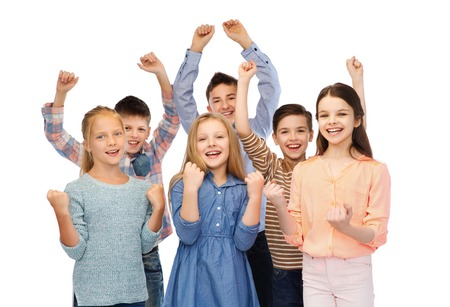 pre adolescent boy: childhood, fashion, gesture and people concept - happy children friends raising fists and celebrating victory