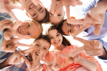 circle of friends: childhood, fashion, friendship and people concept - happy smiling children showing peace hand sign and standing in circle